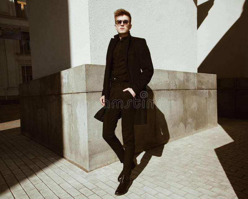 Ein junger Mann steht nahe einem Gebäude lizenzfreies stockbild