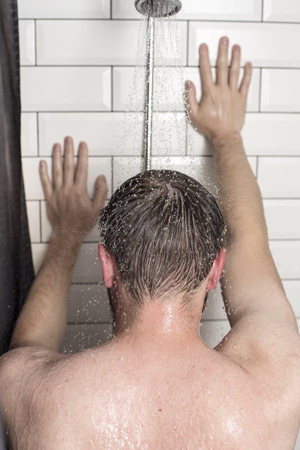Ein junger Mann steht unter der Dusche unter fließendem Wasser und lehnt h lizenzfreie stockbilder