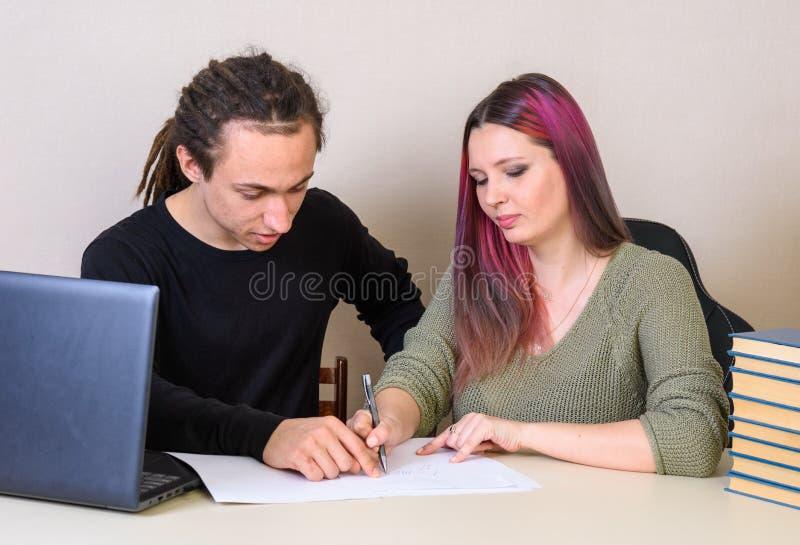 Ein junger Mann stellt auf dar, was das Mädchen auf Papier schrieb lizenzfreies stockfoto