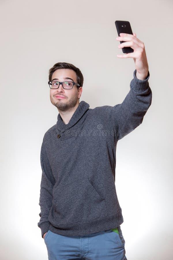 Ein junger Mann tut ein Selbstporträt mit seinem Mobiltelefon stockfoto