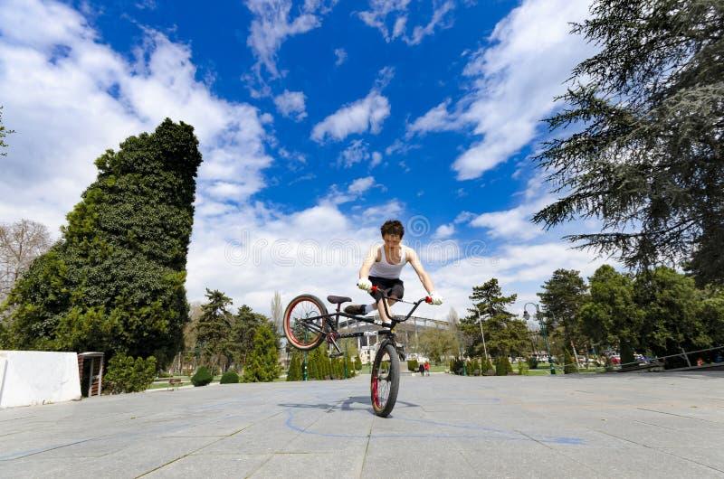 Ein junger Mann tut Tricks auf seinem BMX-Fahrrad lizenzfreies stockfoto