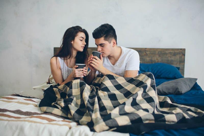Ein junger Mann und eine Frau trinken Kaffee morgens im Bett Romantischer Morgen zu Hause stockfotos