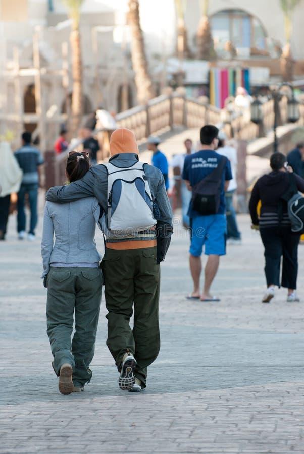 Ein junger Mann und ein Mädchen umfassen entlang einer strandnahen Promenade, während sie Ferien an der Küste genießen lizenzfreies stockbild