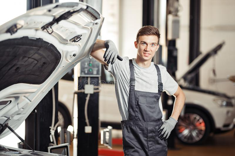 Ein junger Mechaniker steht nahe einem Auto, das er repariert stockfotos