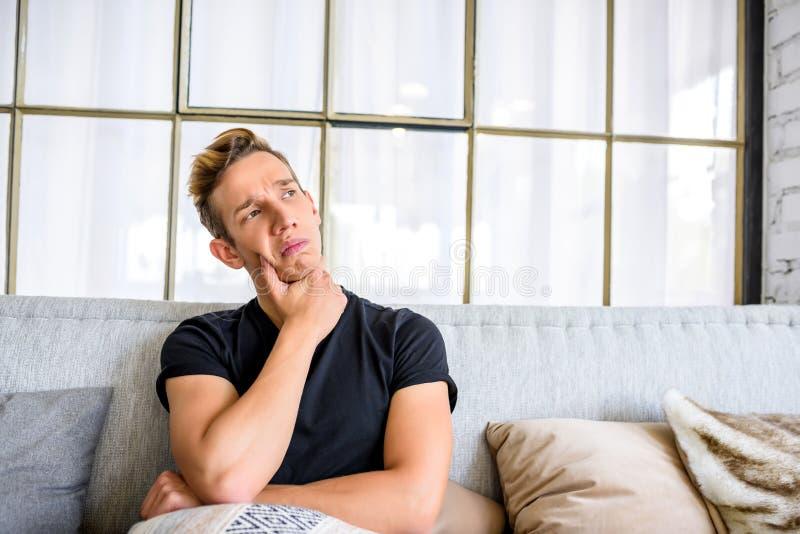 Ein junger nachdenklicher Mann auf dem Sofa in einer Dachbodenartwohnung lizenzfreies stockfoto