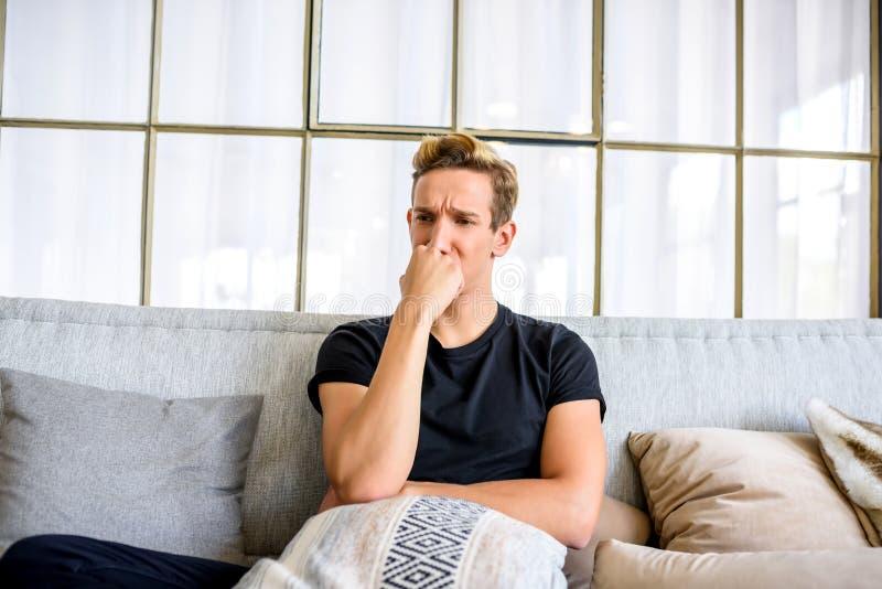 Ein junger nachdenklicher Mann auf dem Sofa in einer Dachbodenartwohnung lizenzfreie stockfotografie