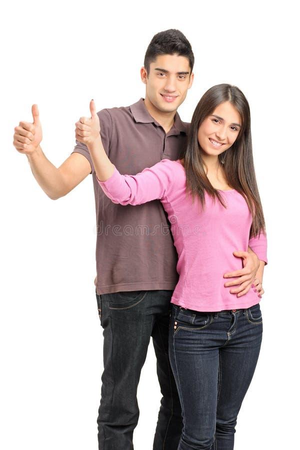 Ein junger Paarstellungsabschluß zusammen und Daumen aufgebend lizenzfreie stockfotos