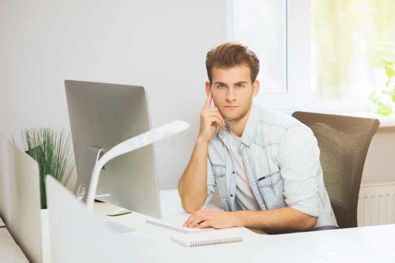 Ein junger Programmierer betrachtet die Kamera Der Grafikdesigner denkt an die zukünftigen Projekte Der junge Kerl lizenzfreie stockfotografie