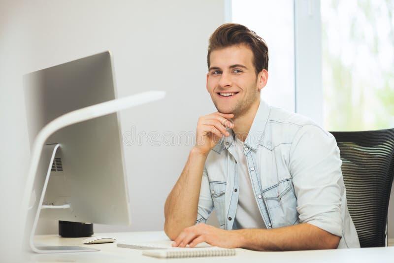 Ein junger Programmierer betrachtet die Kamera Der Grafikdesigner denkt an die zukünftigen Projekte Der junge Kerl stockbilder