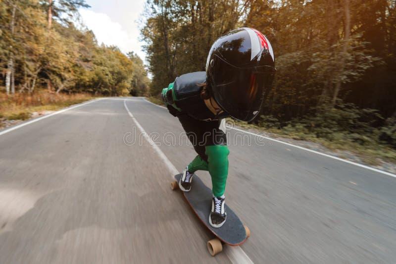 Ein junger Reiter in einer speziellen ledernen Klage und ein Halbsturzhelm fahren an der hohen Geschwindigkeit auf sein longboard lizenzfreies stockbild