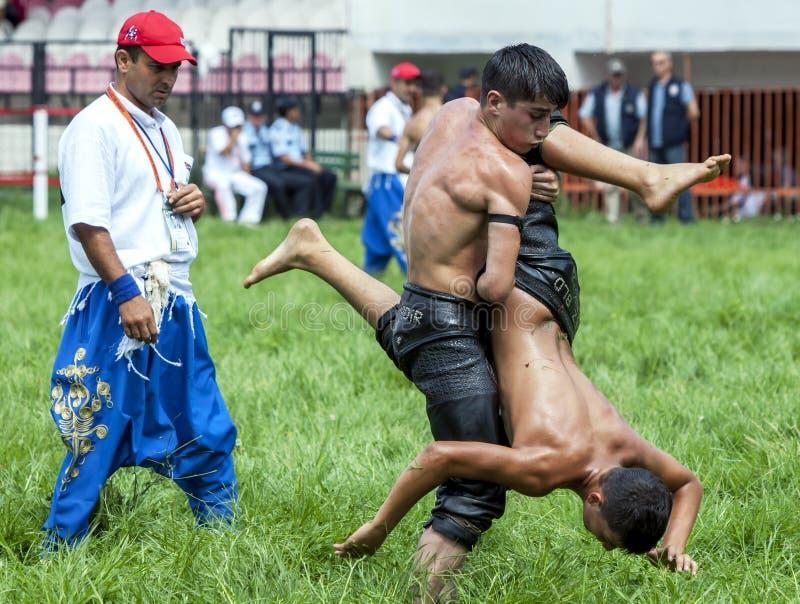 Ein junger Ringkämpfer züchtet seinen Gegner gen Himmel während des Wettbewerbs am türkisches Öl-ringend Festival Kirkpinar in Ed stockfotografie