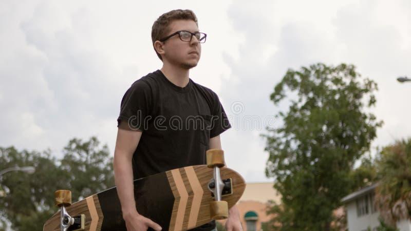 Ein junger Rochen hält sein Skateboard stockfotografie
