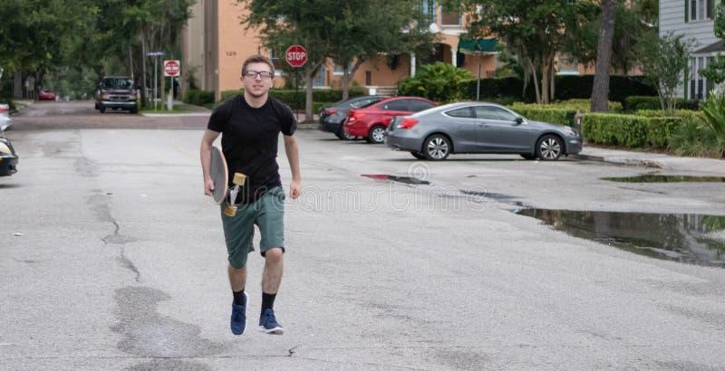 Ein junger Rochen hält sein Skateboard lizenzfreie stockbilder