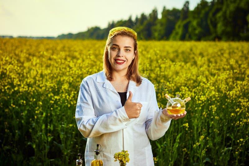 Ein junger schöner Biologe oder ein Agronom überprüft die Qualität des Rapsöls auf einem Rapsfeld Agrargesch?ftskonzept stockfoto