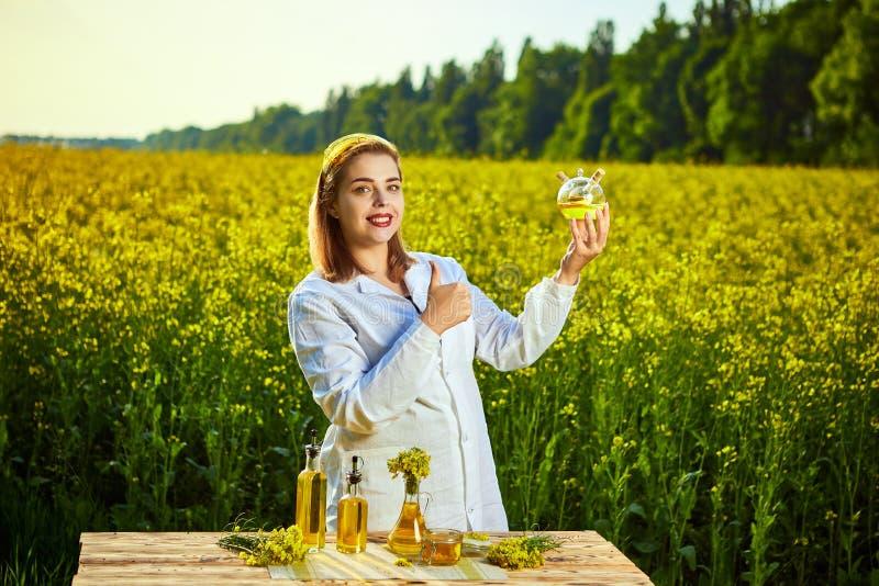 Ein junger schöner Biologe oder ein Agronom überprüft die Qualität des Rapsöls auf einem Rapsfeld Agrargesch?ftskonzept lizenzfreies stockfoto