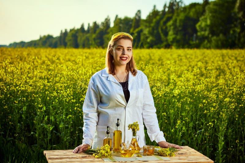 Ein junger schöner Biologe oder ein Agronom überprüft die Qualität des Rapsöls auf einem Rapsfeld Agrargesch?ftskonzept stockfotografie