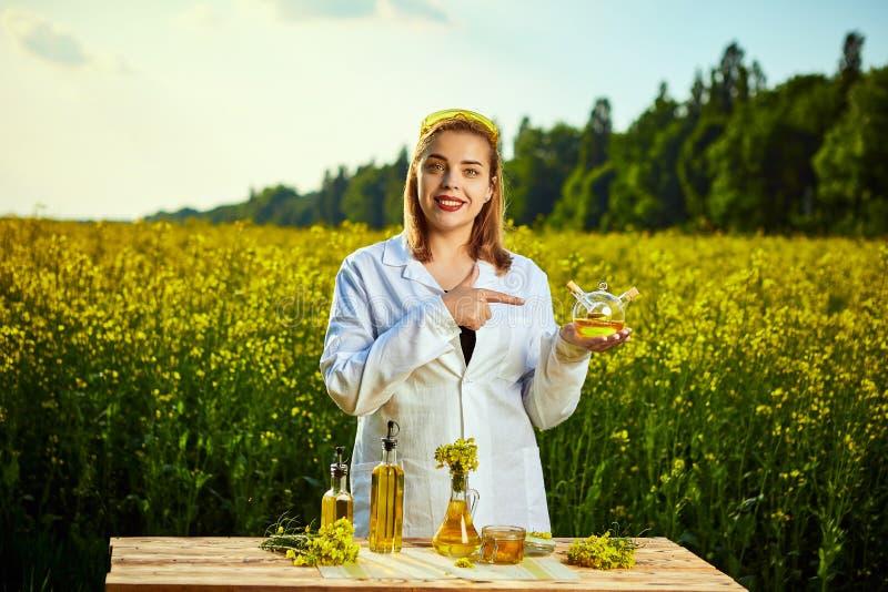 Ein junger schöner Biologe oder ein Agronom überprüft die Qualität des Rapsöls auf einem Rapsfeld Agrargesch?ftskonzept stockfotos
