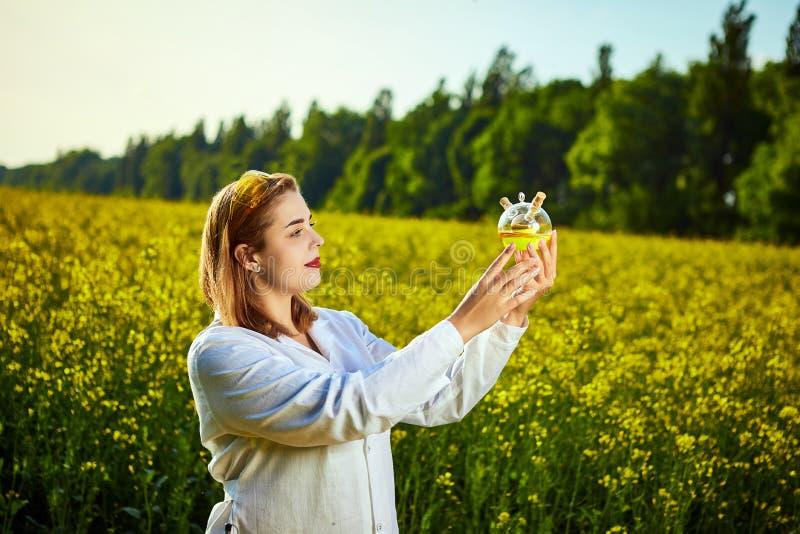 Ein junger schöner Biologe oder ein Agronom überprüft die Qualität des Rapsöls auf einem Rapsfeld Agrargesch?ftskonzept lizenzfreie stockbilder