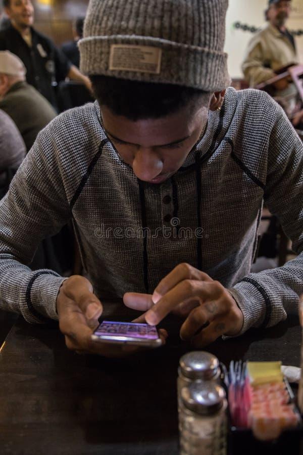 Ein junger, schwarzer Mann simst beim Warten auf seine Mahlzeit an einem Restaurant lizenzfreie stockbilder