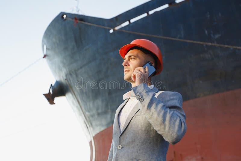 Ein junger stilvoller Mann in einem Schutzhelm gegen den Hintergrund eines Seehafens lizenzfreies stockfoto