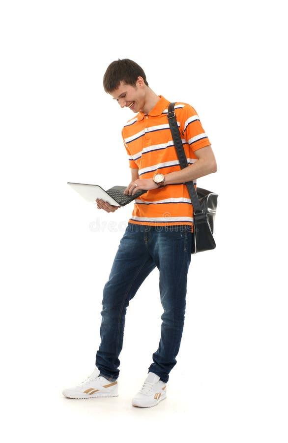 Ein junger Teenager, der einen Laptop anhält stockbild