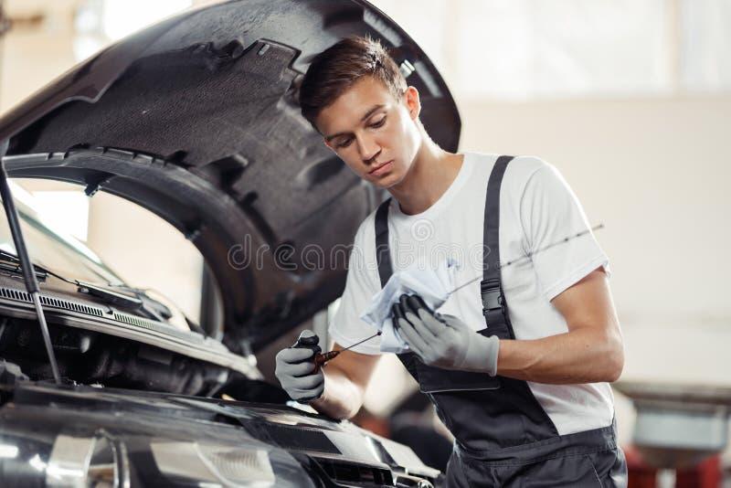 Ein junger und attraktiver Mechaniker überprüft einen Ölstand eines Automotors lizenzfreies stockbild