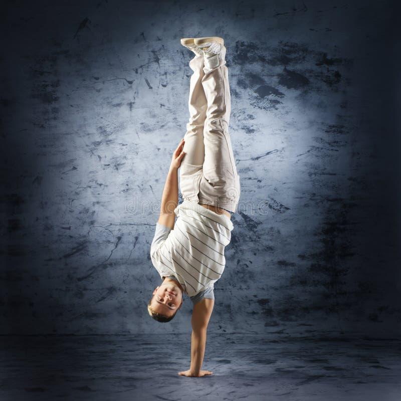 Ein junger und sportlicher Mann, der eine Haltung des modernen Tanzes tut stockfoto