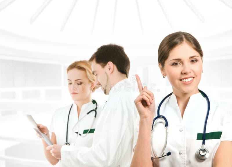 Ein junger weiblicher Doktor vor ihrem Team stockbilder