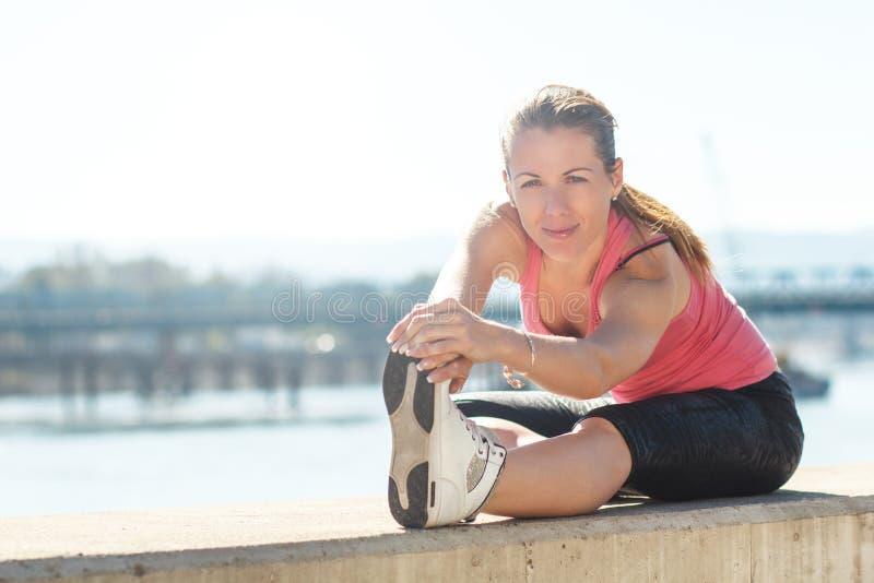 Ein junger weiblicher Läufer, der ihre Muskeln bevor dem Rütteln ausdehnt stockfotografie