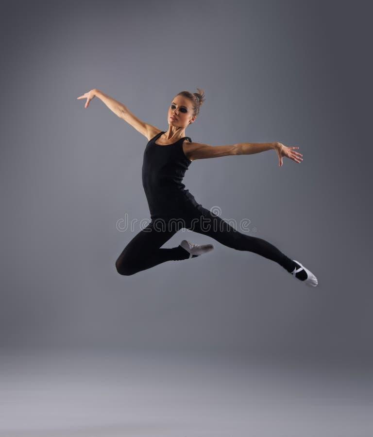 Ein junger weiblicher Tänzer fing in einem Sprung lizenzfreie stockfotos