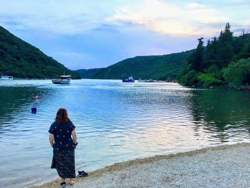 Ein junger weiblicher Tourist, der die schönen Ansichten von Lim, Kroatien an einem ruhigen ruhigen Abend bewundert Die Lim-Bucht stockfoto