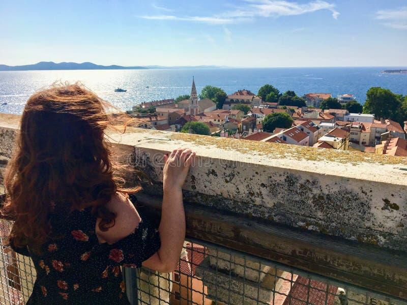 Ein junger weiblicher Tourist an der Spitze des Glockenturms in der alten Stadt von Zadar, Kroatien, heraus betrachtend der schön lizenzfreies stockfoto