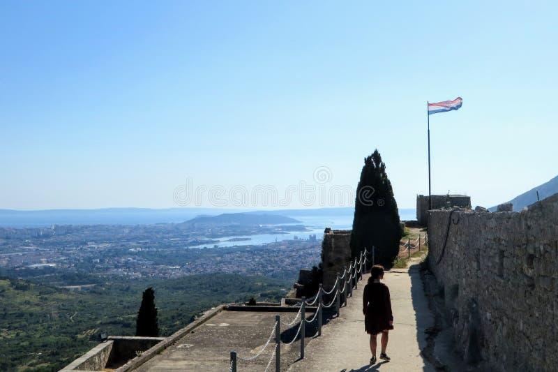 Ein junger weiblicher Tourist, der um die mittelalterliche Festung von Klis an einem schönen Sommertag geht stockbilder