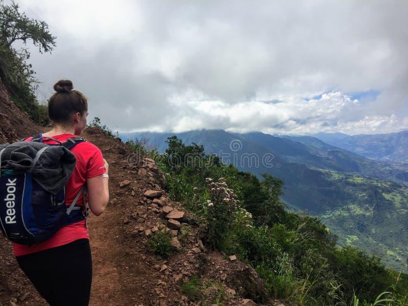Ein junger weiblicher Wanderer beginnt auf ihrer Wanderung durch die Täler und die Berge der Anden stockfotos