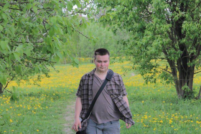 Ein junger wohlgenährter Mann geht durch eine Frühlingswiese mit hellgrünem jungem Gras, Bäumen und blühendem Löwenzahn stockfoto
