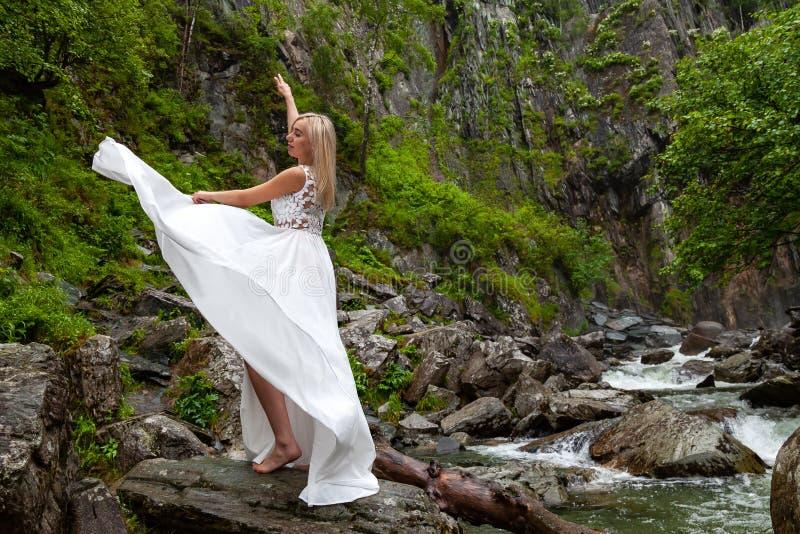 Ein junges blondes Mädchen in einer eleganten Haltung zieht ein Boudoirkleid in den Bergen gegen einen Wasserfall und Steine hoch lizenzfreies stockbild
