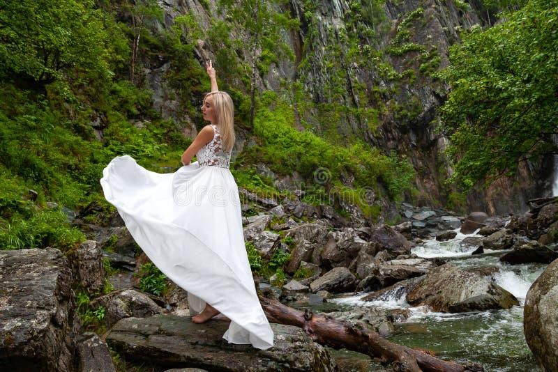 Ein junges blondes Mädchen in einer eleganten Haltung zieht ein Boudoirkleid in den Bergen gegen einen Wasserfall und Steine hoch stockbilder
