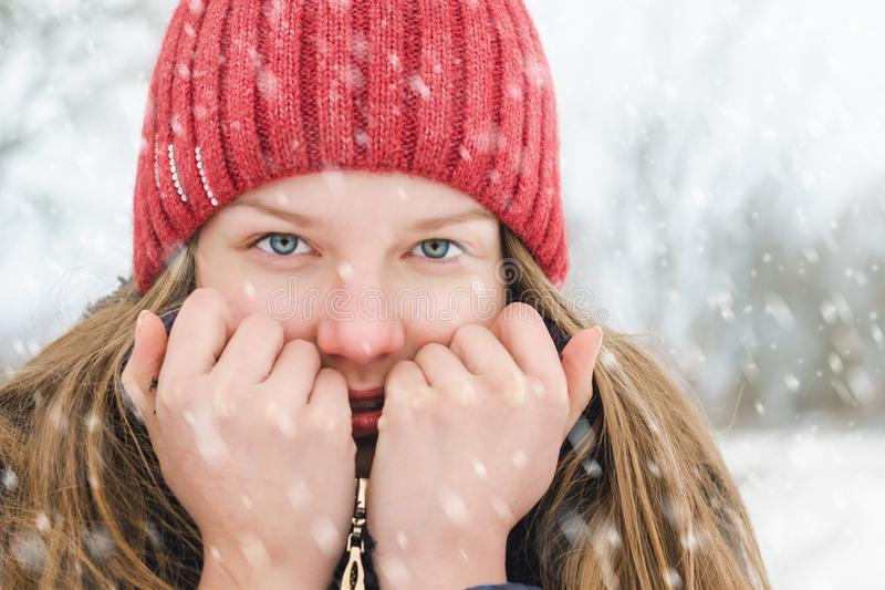 Ein junges blondes Mädchen hält einen Kragen in ihren Händen, um ihn wärmer zu machen und lächelt unter weichem flaumigem Schnee  stockfoto