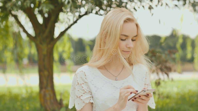 Ein junges blondes Mädchen schreibt am weißen Telefon in einem Stadtpark stockbilder