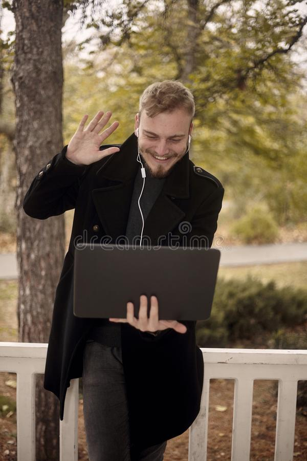 Ein junges in der Hand l?cheln und gl?cklicher Mannholdinglaptop, jemand gr??end, das mit einem gestikuliert, hoben an, Videokonf lizenzfreies stockbild