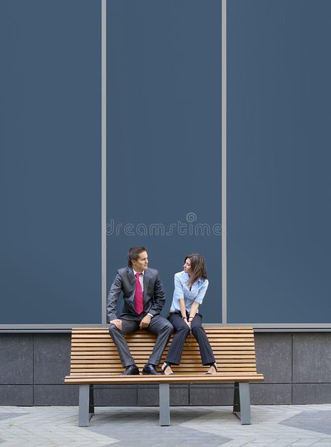 Ein junges Geschäftspaar, das auf einer Bank sitzt lizenzfreies stockbild