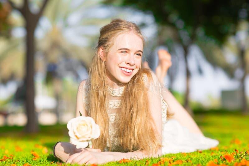 Ein junges hübsches Mädchen, das eine weiße Rose in einem sonnigen Park hält stockfoto
