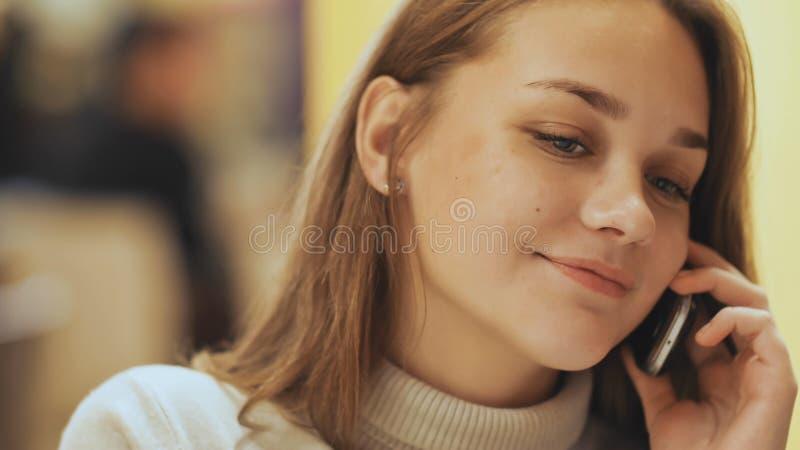 Ein junges hübsches Mädchen liest und schreibt Mitteilungen am Telefon, das in ein Café am Tisch sitzt Nahaufnahme lizenzfreie stockfotos