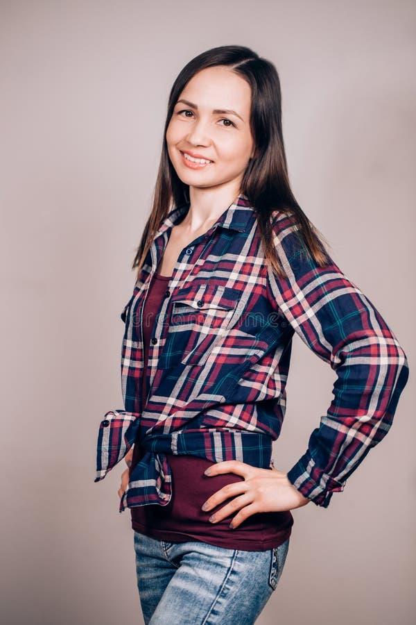 Ein junges Hippie-Mädchen auf grauem Hintergrund Junge Leute, Studenten des Konzeptes lizenzfreies stockbild