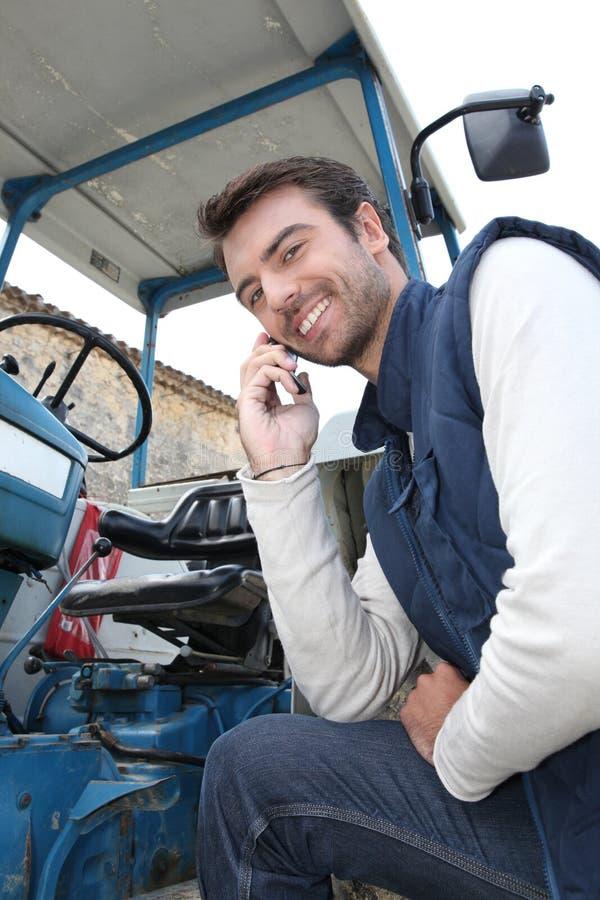 Ein junges Landwirttelefonieren stockbilder
