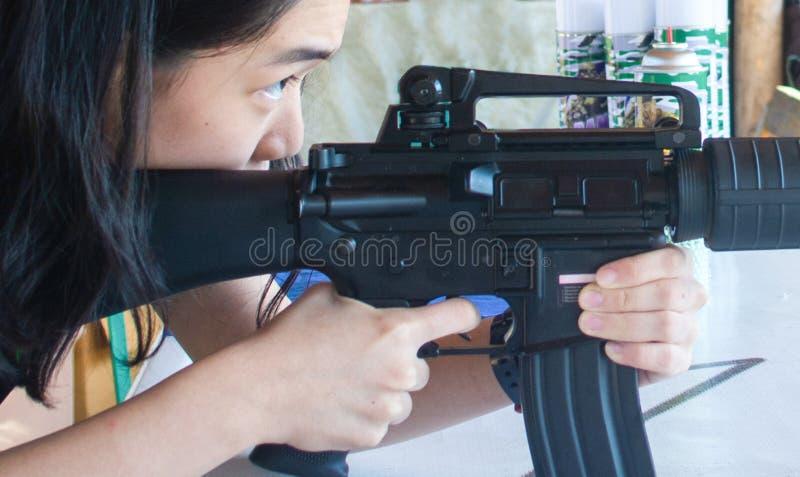 Ein junges Mädchen, das ein Luftgewehr auf ein Ziel schießt lizenzfreie stockfotografie