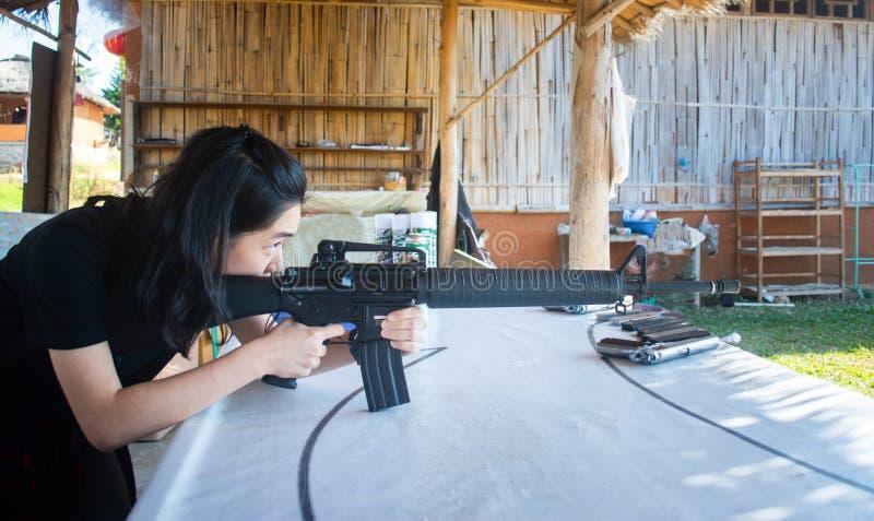 Ein junges Mädchen, das ein Luftgewehr auf ein Ziel schießt stockbild