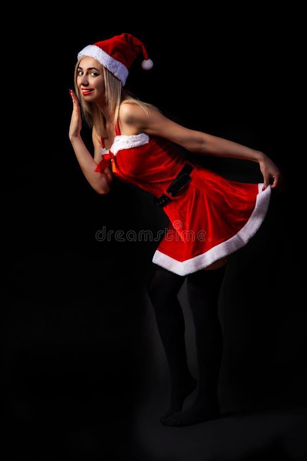 Ein junges Mädchen, das als Santa Claus gekleidet wird, steht gegen einen dunklen Hintergrund mit einer verlegenen Hand, die ihre stockfoto