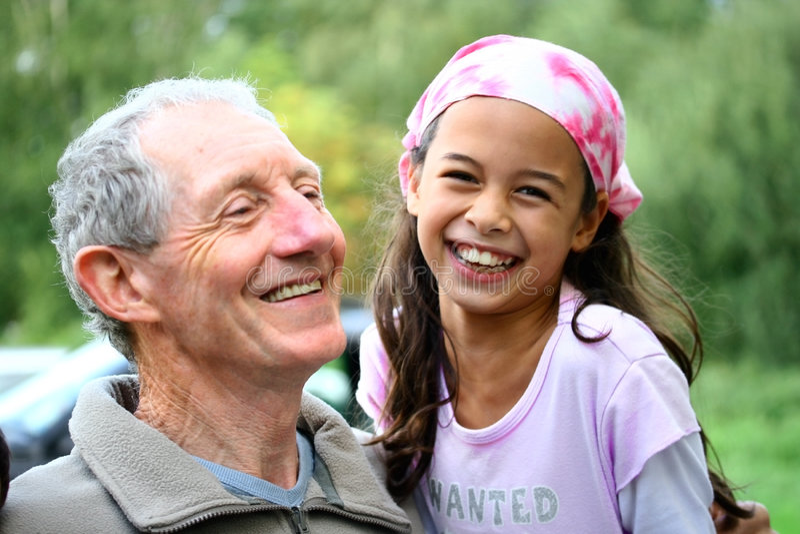 Ein junges Mädchen, das einen Witz mit ihrem Großvater teilt stockbilder