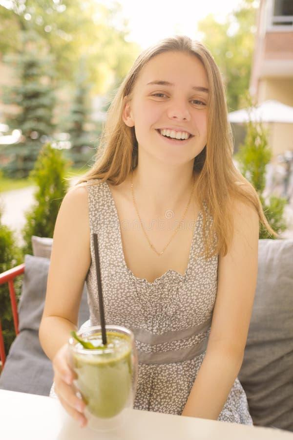 Ein junges Mädchen in einem Café im Freien trinkt einen grünen Smoothie und ein Lächeln Das Konzept des gesunden Lebensstils und  lizenzfreie stockfotografie